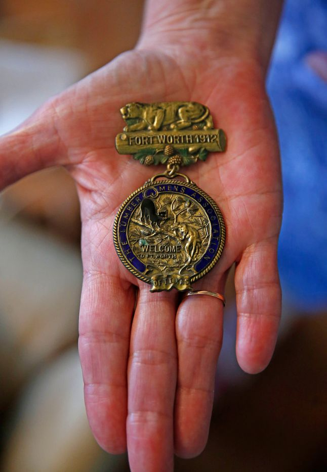 Tarrant County historian Carol Roark shows a Lumbermen's Association badge from 1912 at collector Larry Schuessler's home in Fort Worth.
