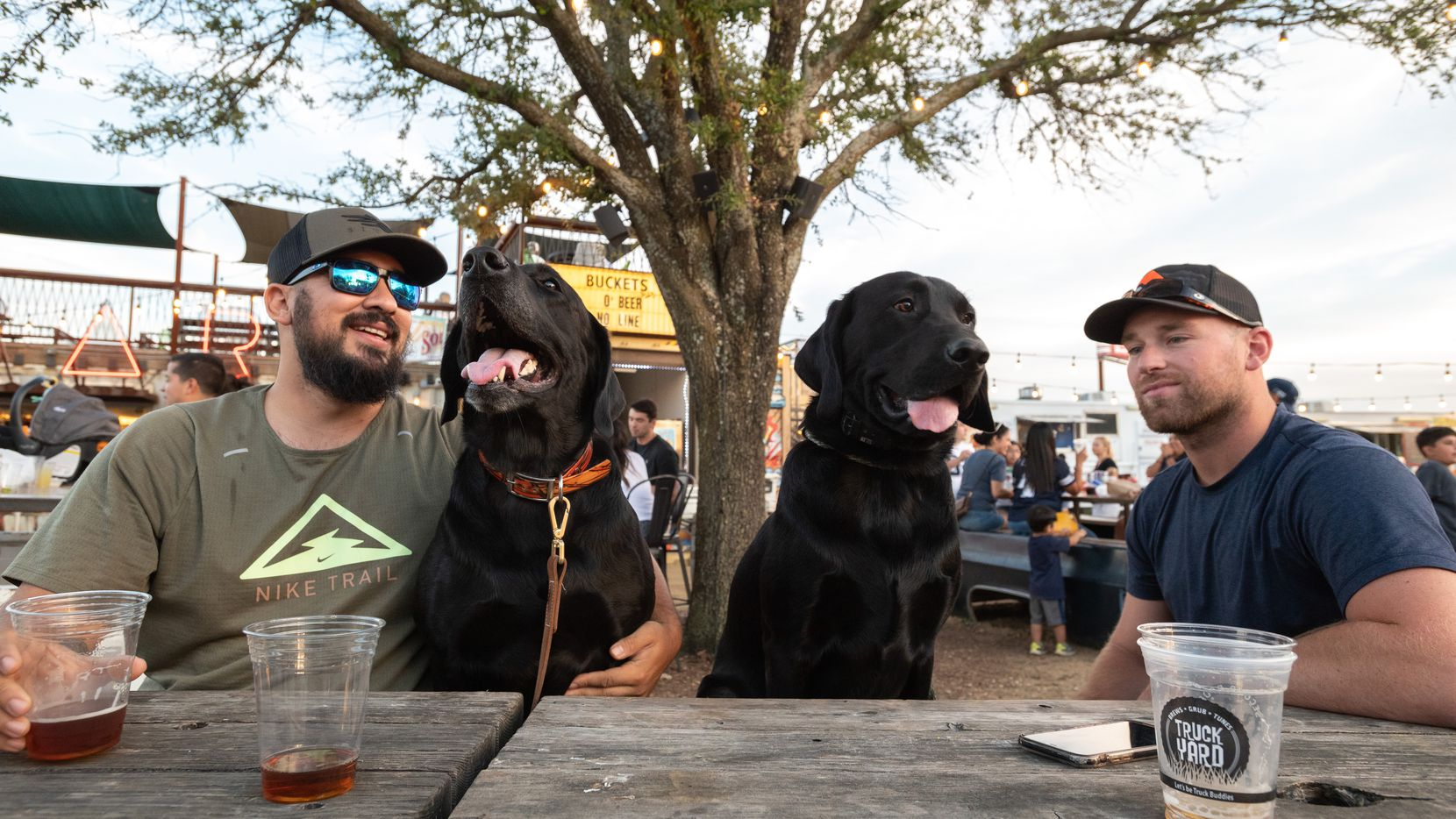 Louis Perez, left, with his dog Goose, and their buddies Bingham and Michael Swayne, have a couple of beers at Truck Yard. It's among 26 restaurants in Grandscape, a $1.5 billion development in The Colony.