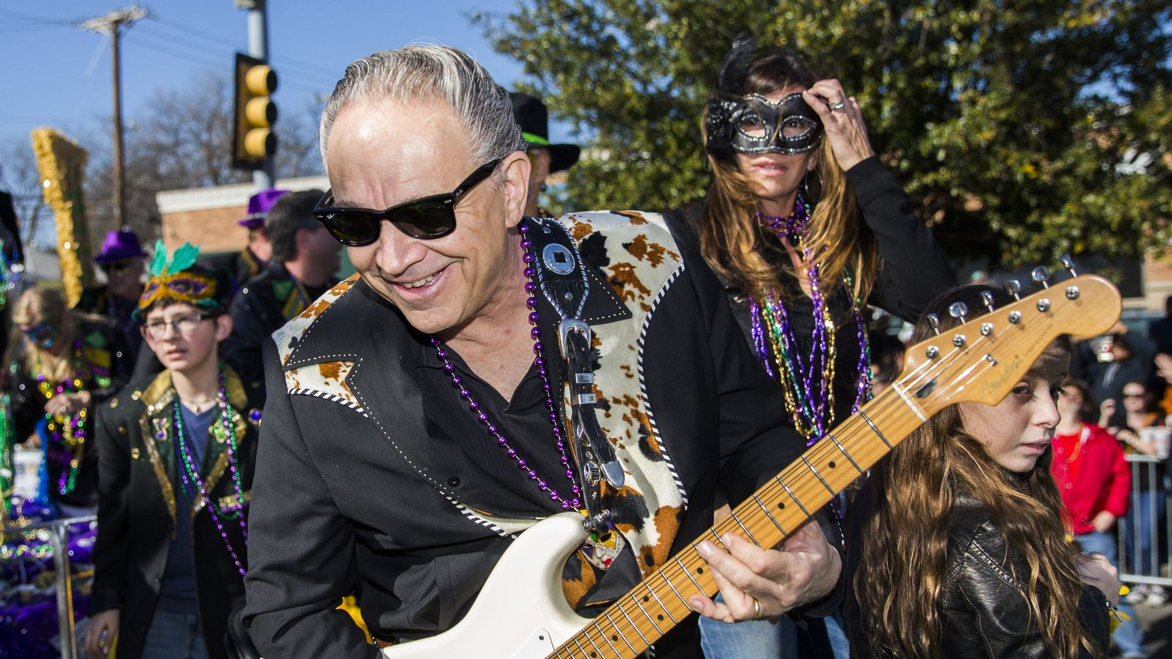 Jimmie Vaughan played guitar on a float during the annual Oak Cliff Mardi Gras parade in 2016. Vaughan said Tuesday he'd tested negative for COVID-19.