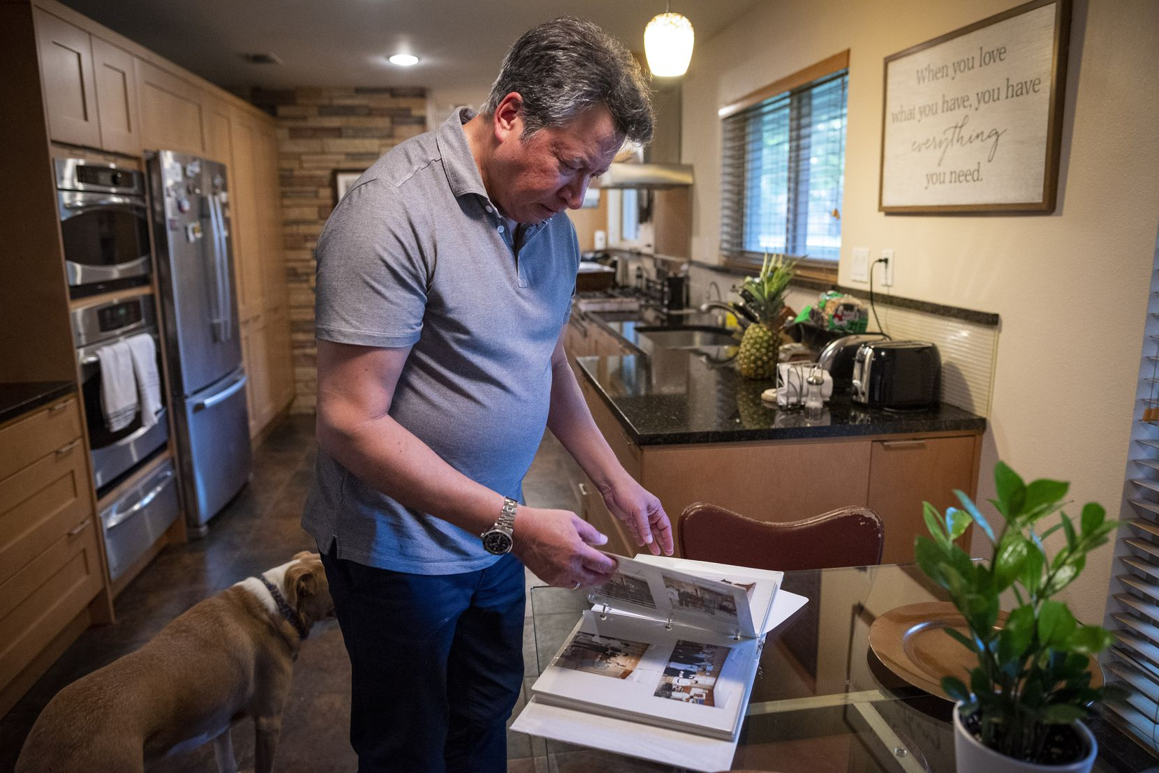 Benjamin Salazar looks through old pictures from his family's time living in New York, at his home in Dallas. Benjamin used to work for American Express at the World Trade Center Plaza in New York City.