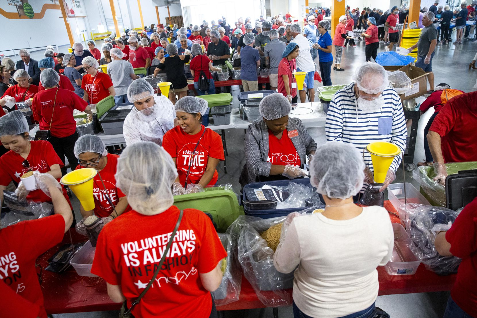 Volunteers from Macy's package food as they volunteer at North Texas Food Bank in Plano on Sept. 11, 2019. The volunteer work was part of Freedom Day, a community service day put on by Communities Foundation of Texas and 9/11 Day. (Shaban Athuman/Staff Photographer)