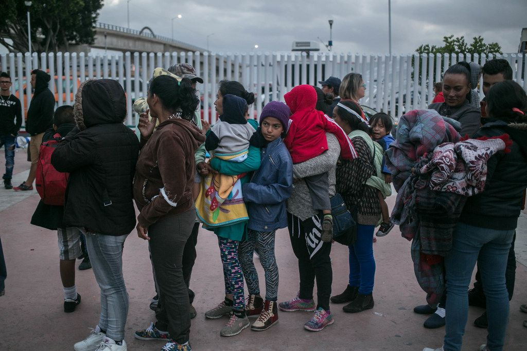 A caravan of migrants from Central America who traveled through Mexico lineup outside Tijuana's pedestrian west border crossing with the U.S., in Mexico, April 29, 2018. The migrants were told Sunday afternoon that the immigration officials could not process their claims, and they would have to spend the night on the Mexican side of the border.