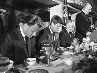 President John F. Kennedy and others at the head table bow their heads during the invocation at the annual Presidential prayer breakfast in a Washington hotel, Feb. 9, 1961. From Left are Evangelist Billy Graham, Kennedy; Sen. Frank Carlson, R-Kan., and Judge Boyd Leedom of Washington, President of the International Christian Leadership Conference, the sponsoring organization. (AP Photo/Henry Burroughs)