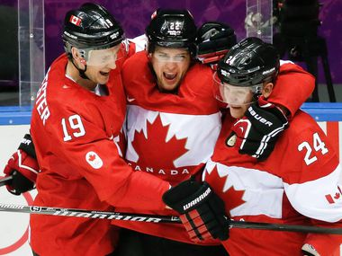 Canada forward Jamie Benn, center, celebrates his goal against the USA with teammates Jay Bouwmeester, left, and Corey Perry, right, during the second period of the men's semifinal ice hockey game at the 2014 Winter Olympics, Friday, Feb. 21, 2014, in Sochi, Russia.