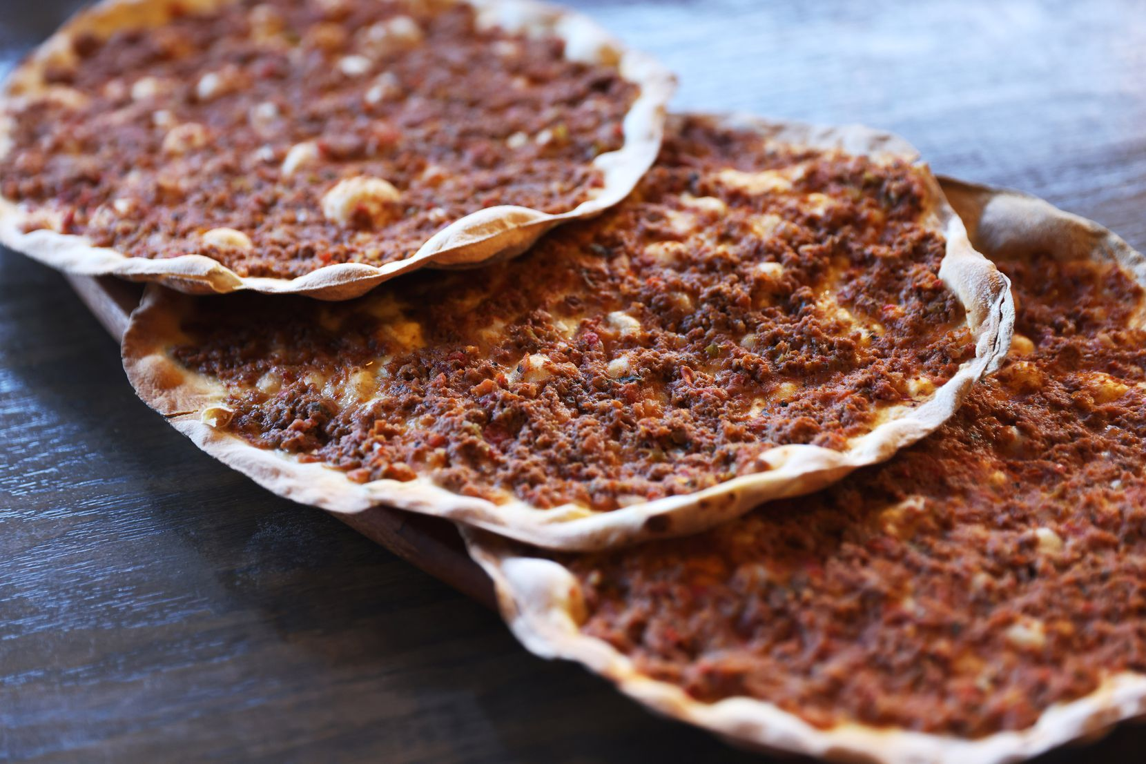 Lahmacuns have a very thin crust and are topped with a mixture of minced beef, tomatoes, onion, bell pepper and parsley. They do not include cheese.