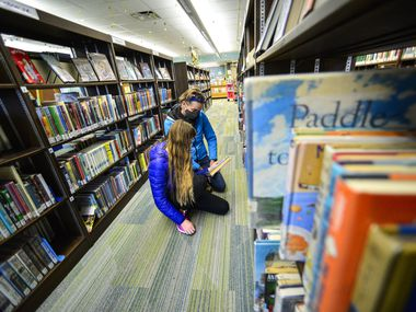People select a library book in this file photo. The Keller Public Library recently decided to end a partnership with Fort Worth after 22 years.