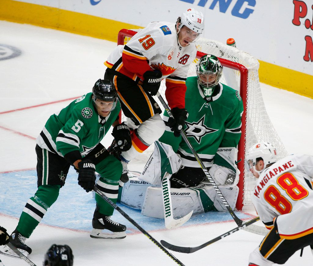 Calgary Flames left wing Matthew Tkachuk (19) leaps to clear room as Dallas Stars defenseman Andrej Sekera (5) and goaltender Ben Bishop (30) defend during the third period of an NHL hockey game in Dallas, Thursday, Oct. 10, 2019. (AP Photo/Michael Ainsworth)