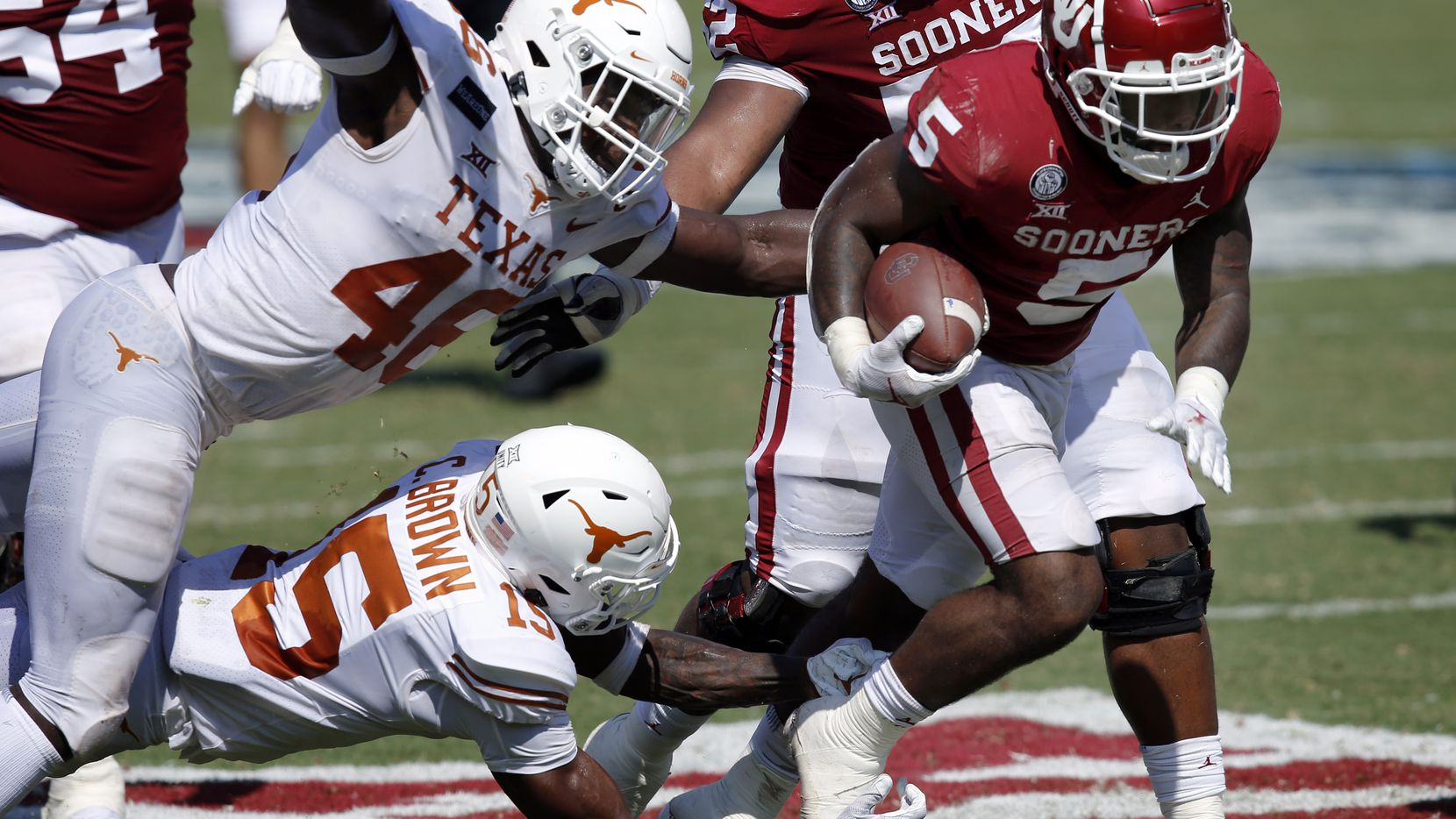 Texas Longhorns linebacker Joseph Ossai (46) and defensive back Chris Brown (15) combine to force a fumble by Oklahoma Sooners running back T.J. Pledger (5) during the second quarter of the Red River Rivalry at the Cotton Bowl in Dallas, Saturday, October 10, 2020. Oklahoma won in quadruple overtime, 53-45. (Tom Fox/The Dallas Morning News)