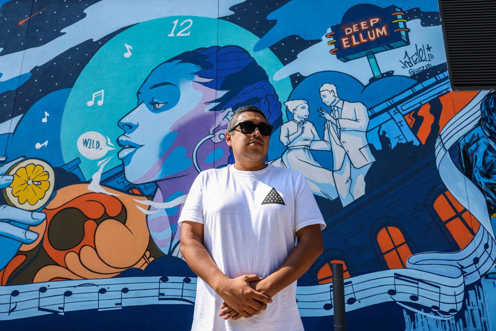 """Hatziel Flores poses by his creation """"Blues of the big night"""" in the alley."""