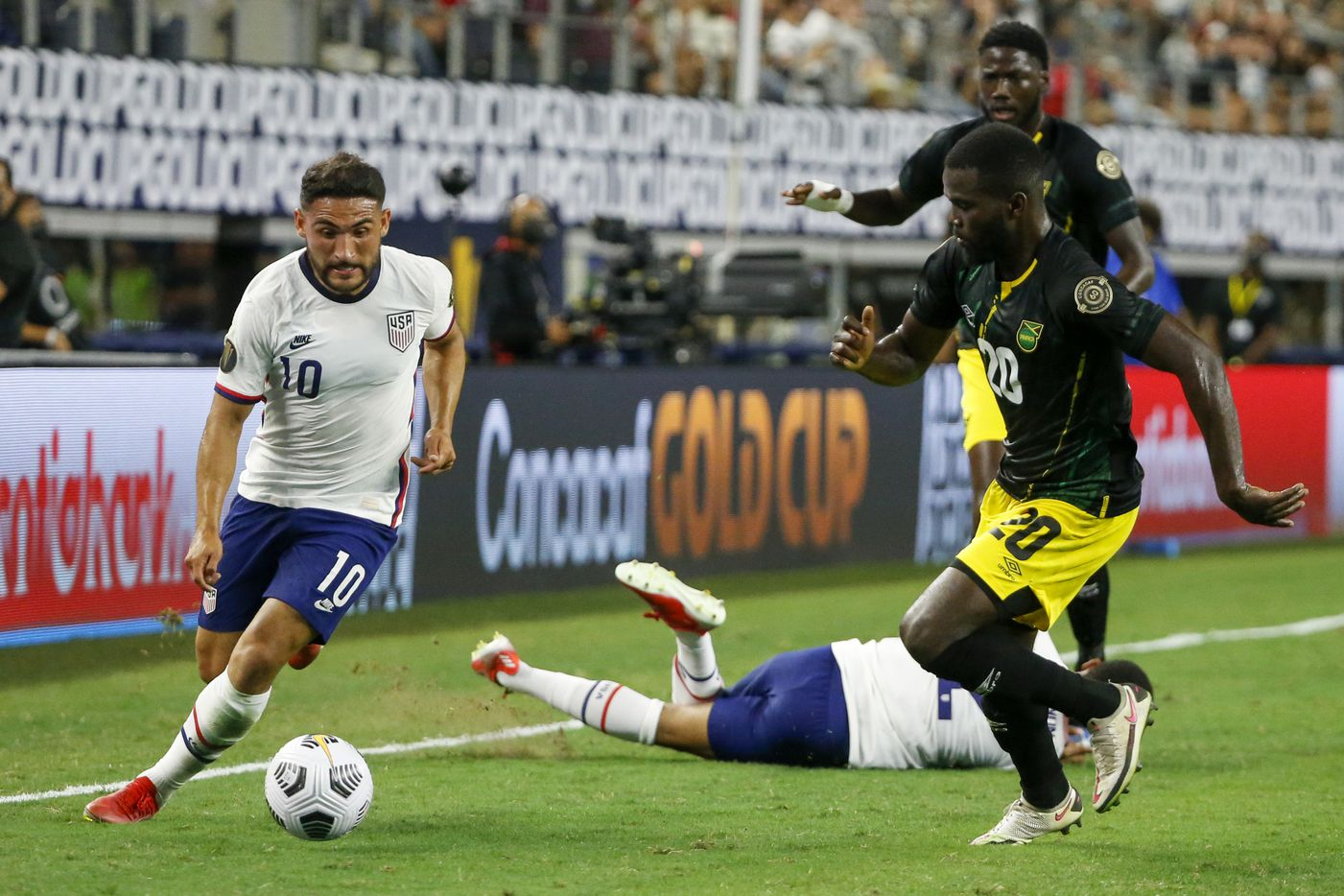 USA midfielder Cristian Roldan (10) dribbles around Jamaica defender Kemar Lawrence (20) during the second half of a CONCACAF Gold Cup quarterfinal soccer match at AT&T Stadium on Sunday, July 25, 2021, in Arlington. (Elias Valverde II/The Dallas Morning News)