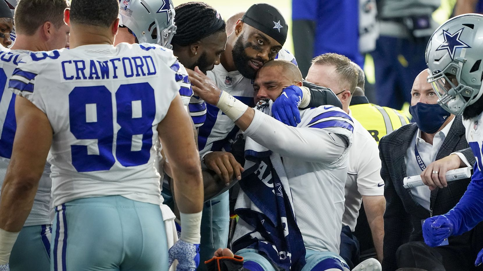 Dallas Cowboys quarterback Dak Prescott lis consoled by teammates as he leaves the field on a cart after beig injured on a tackle by New York Giants cornerback Logan Ryan during the third quarter of an NFL football game at AT&T Stadium on Sunday, Oct. 11, 2020, in Arlington. Prescott was injured o the play when Ryan came down on his right leg and left the game. (Smiley N. Pool/The Dallas Morning News)