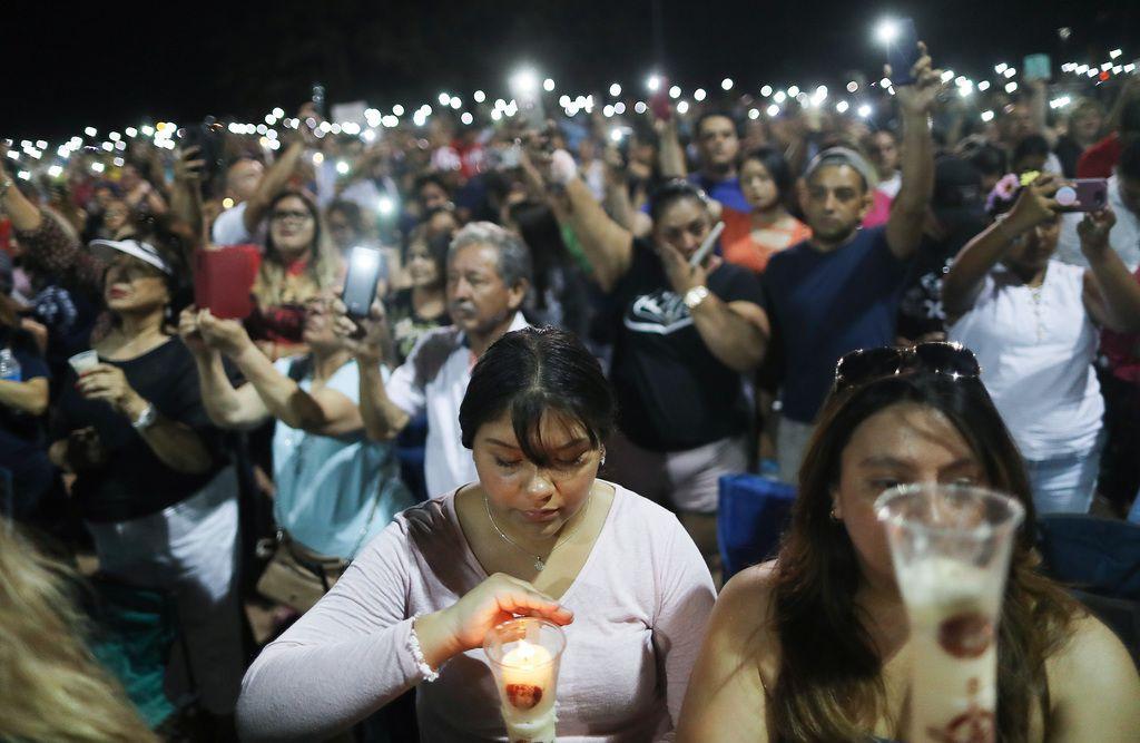 La gente usa sus teléfonos y veladores durante una vigilia en El Paso, el domingo, luego de un tiroteo en el que murieron al menos 21 personas.