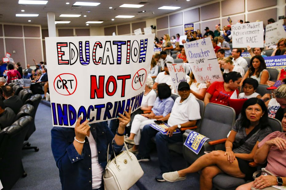 Protesters held signs Tuesday before the FWISD board meeting in Fort Worth. (Juan Figueroa/The Dallas Morning News)