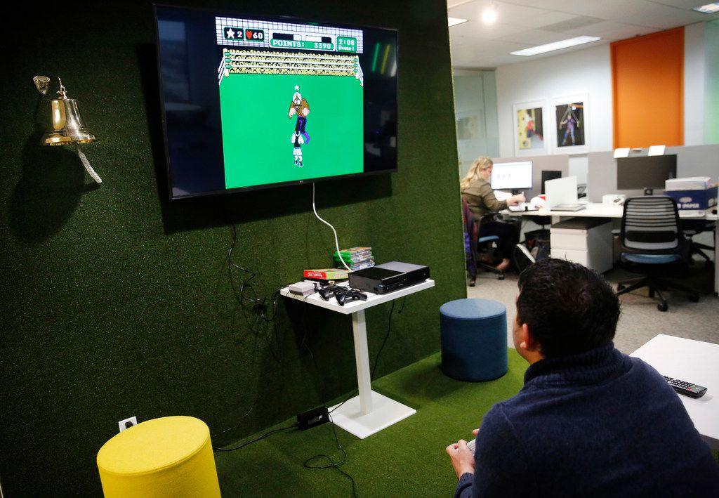 Marketing coordinator Oscar Romero plays video games between phone calls and emails.