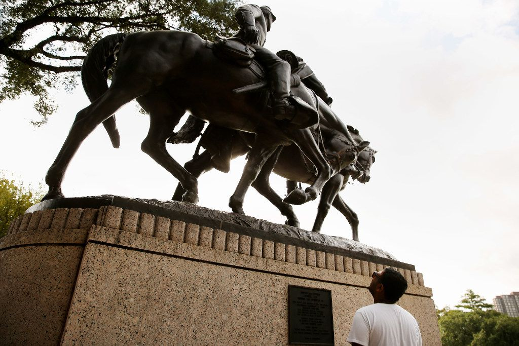 Fawaz Anwar of Carrollton looks up at a statue of Confederate Gen. Robert E. Lee at Lee Park in the Oak Lawn neighborhood.