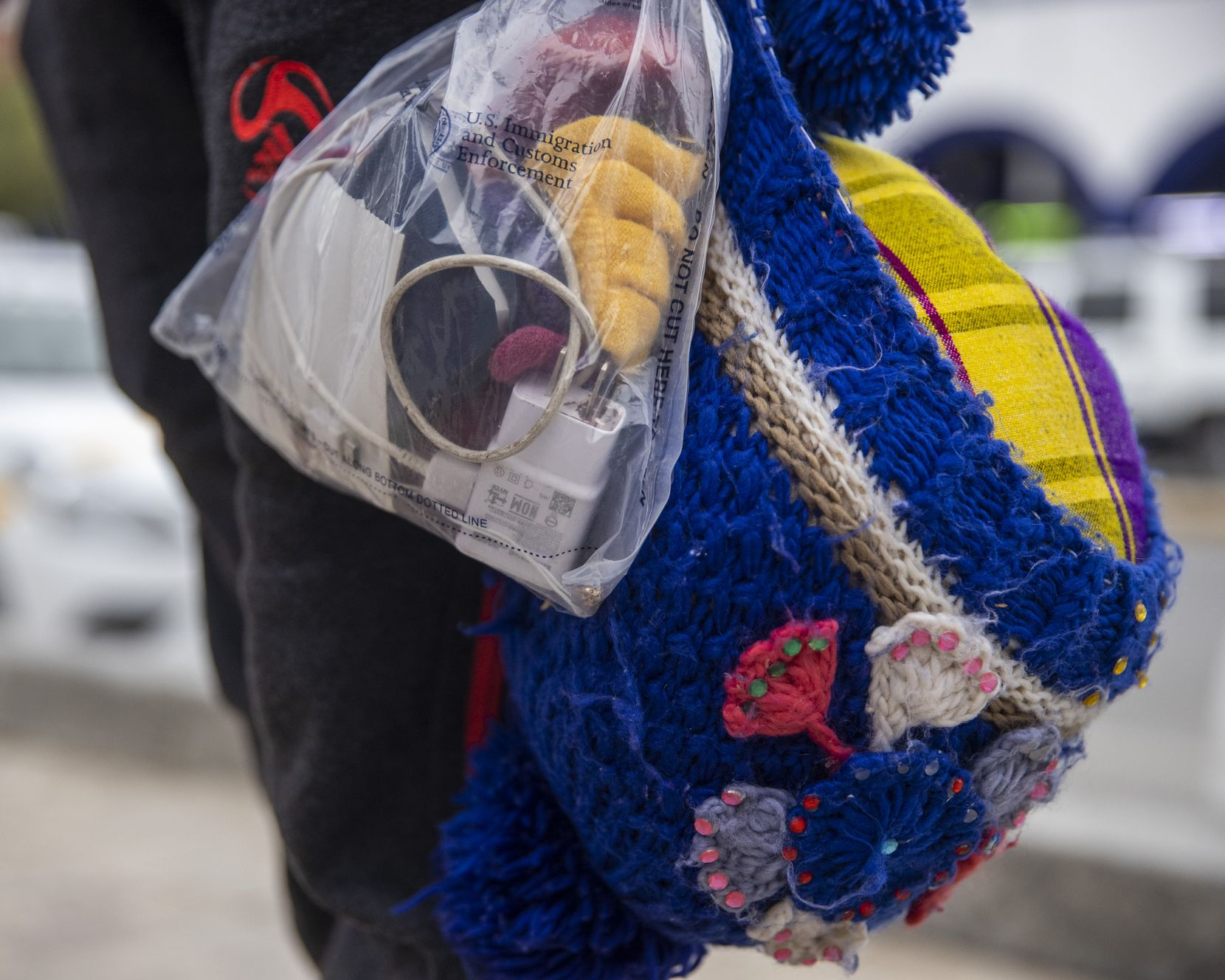 Isabela Julaj holds her few belongings in a U.S. government-provided plastic bag and a knit bag as she waits with other migrant families stranded in the plaza near the international bridge in Reynosa, Mexico.