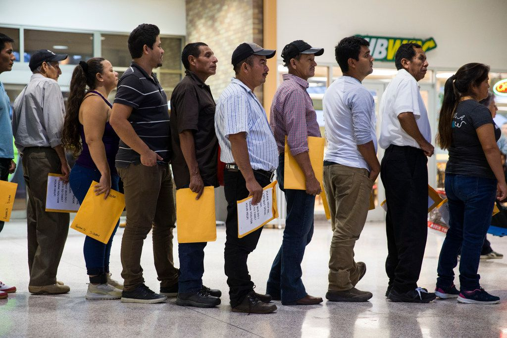 Immigrants wait to get their bus tickets after at the bus station at McAllen, Texas on June 10, 2018.
