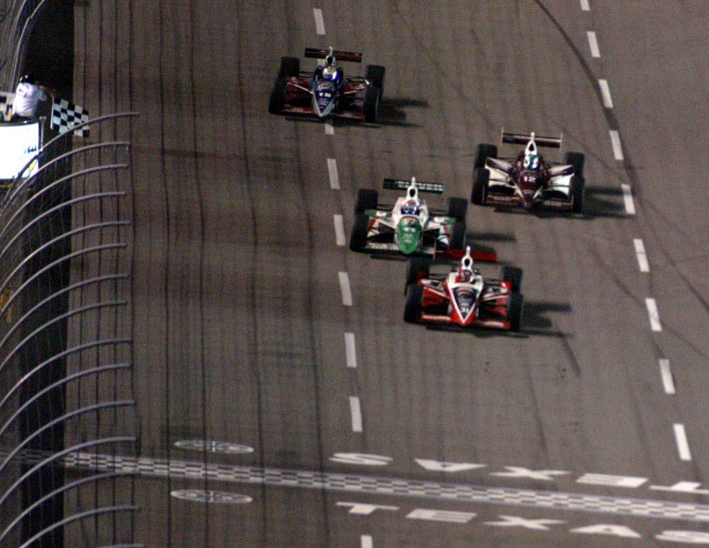 Al Unser Jr. takes the checkered flag in front of #11 Tony Kanaan during the IRL IndyCar Series Bombardier 500 at the Texas Motor Speedway, Saturday, June 7, 2003.