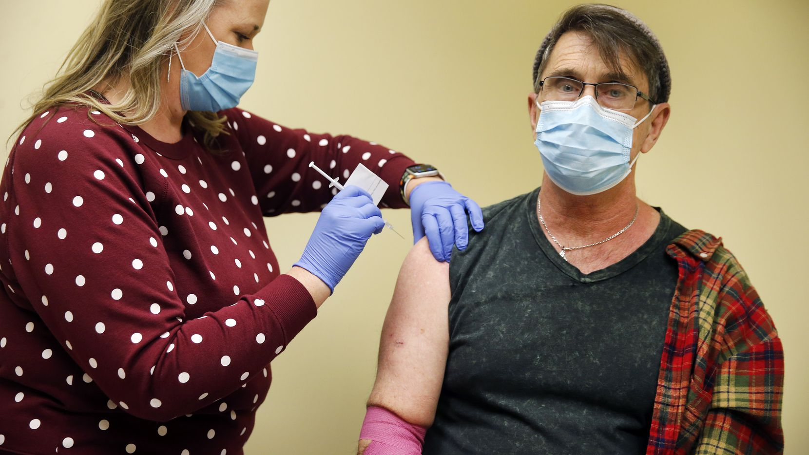 Clinical research project manager Jody Rogers administers the second of two AstraZeneca Phase III COVID trial shots to Robert Lynn of Dallas at the Prism Health North Texas location in Oak Cliff, Thursday, December 3, 2020. Lynn, a public health volunteer, doesn't know if he received the vaccine or a placebo. (Tom Fox/The Dallas Morning News)