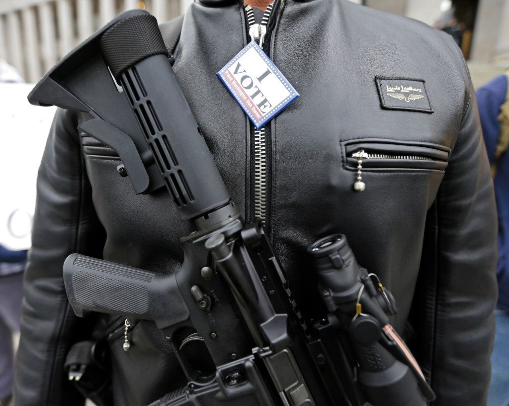 """In this Jan. 15, 2015 file photo, Mark Ramirez of Bainbridge Island, Wash., wears his Colt M4 gun and a button that reads """"I Vote - Proud Washington Gun Owner,"""" during a gun-rights rally at the Capitol in Olympia, Wash. Washington is one of four states putting initiatives before voters in the 2016 election that would broaden background checks or restrict who can buy guns and ammunition. (AP Photo/Ted S. Warren, File)"""