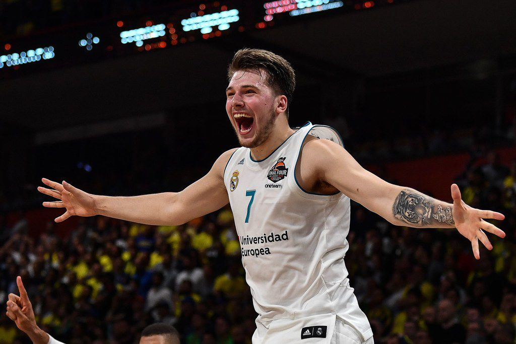 Real Madrid's Slovenian Luka Doncic (C-7) jumps over the barrier as the team celebrates their 85-80 win over Fenerbahce in the Euroleague Final Four finals basketball match between Real Madrid and Fenerbahce Dogus Istanbul at The Stark Arena in Belgrade on May 20, 2018.