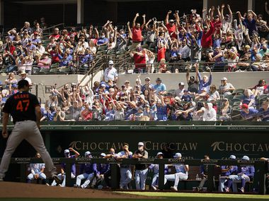 Fans do the wave as Baltimore Orioles starting pitcher John Means looks for a sign during the sixth inning against the Texas Rangers at Globe Life Field on Sunday, April 18, 2021.