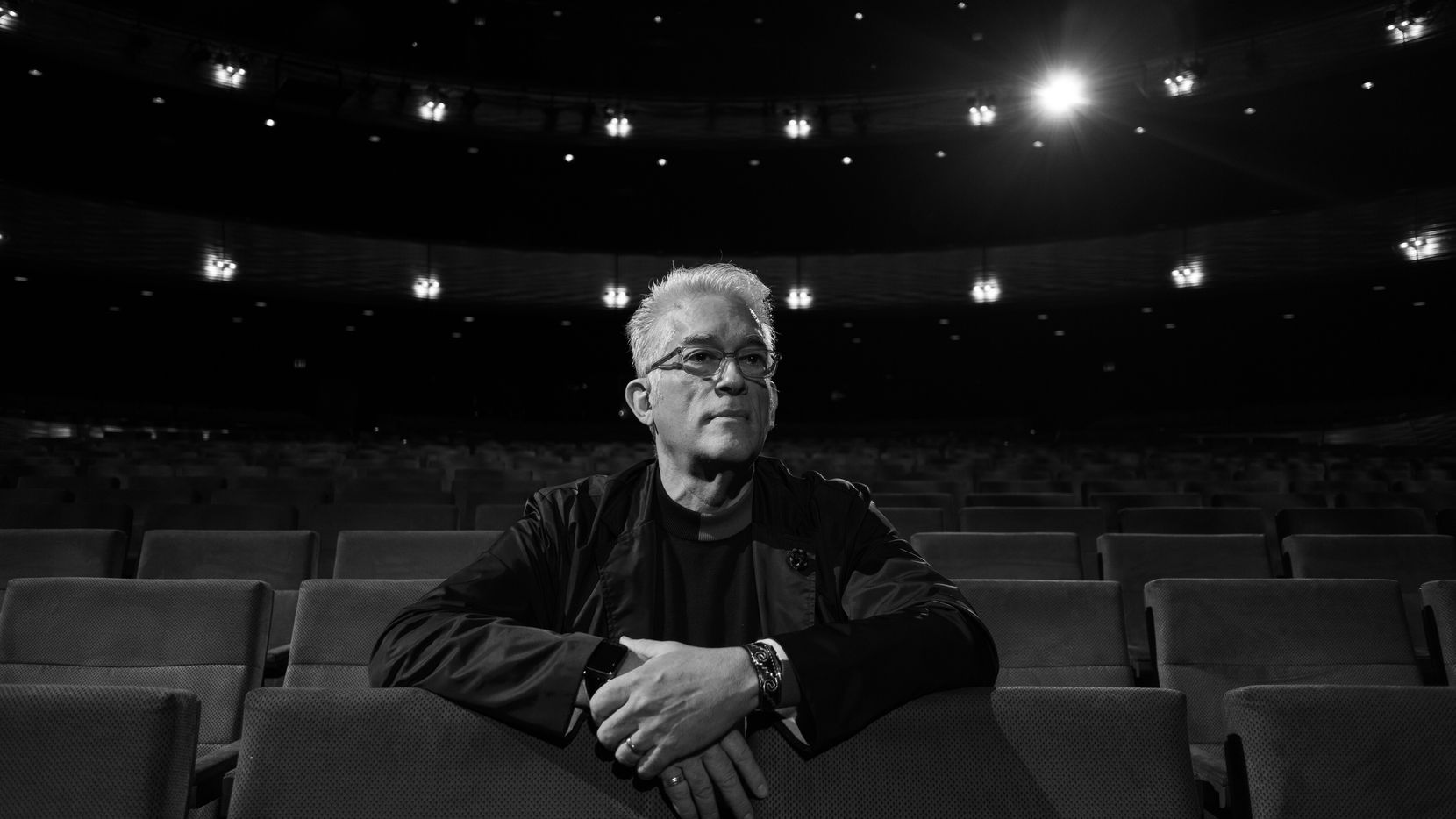 Executive Director at TITAS/Dance Unbound Charles Santos sits in a theater in Dallas.