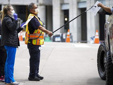 Health care workers use a pole to transfer paperwork to a person being tested at a COVID-19 drive-through testing site at American Airlines Center on Monday, April 20, 2020, in Dallas. Officials say daily tallies of include old and new cases.