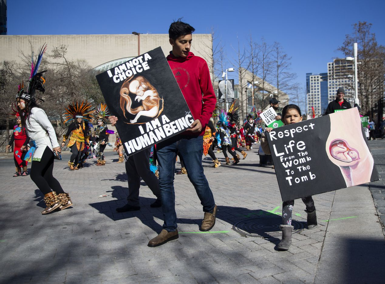Jose Lazalde (center), 16, and his sister Lordes Lazalde, 5, march from the the Cathedral Santuario de la Virgen de Guadalupe to the Earle Cabell Federal Courthouse during the North Texas March for Life on Saturday, Jan. 18, 2020.