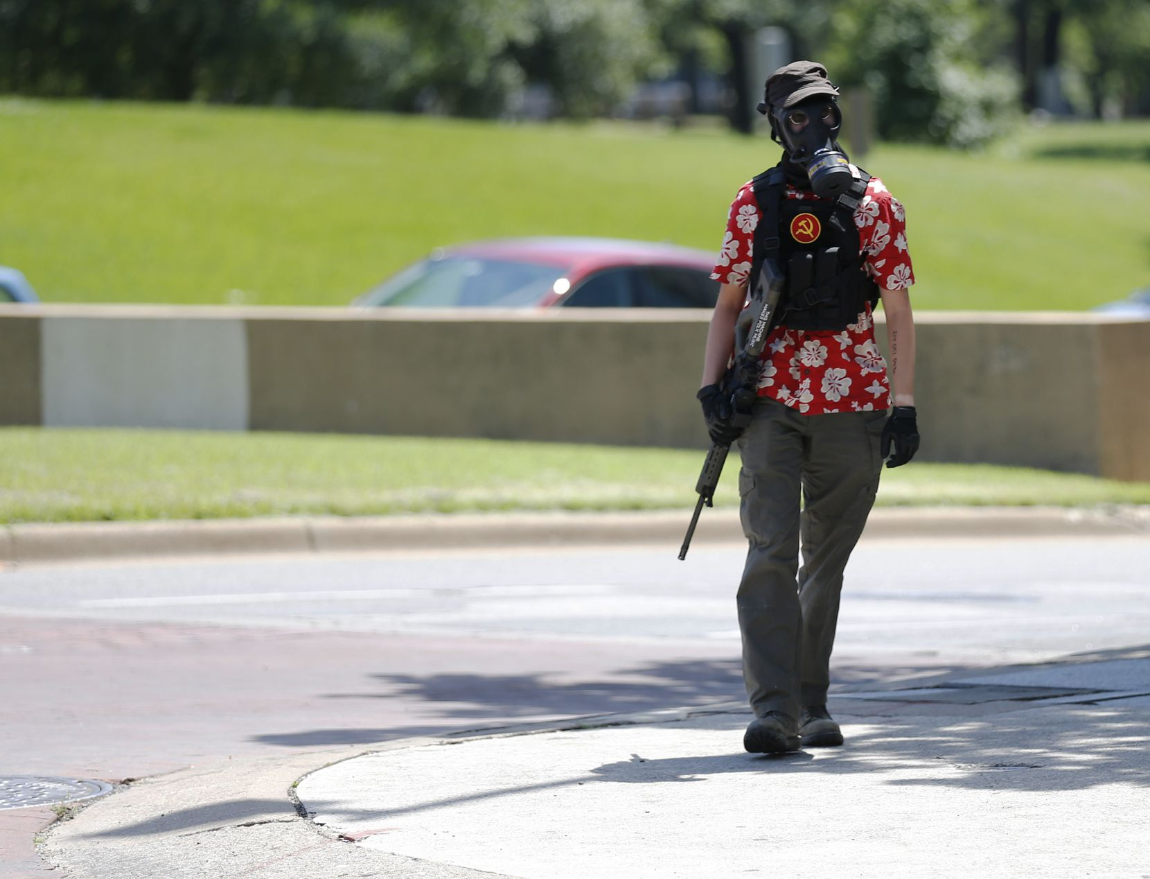 "A person wearing a Hawaiian shirt and carrying a rifle appeared during a protest demonstration against police violence at Dallas City Hall on May 30, 2020. People outfitted similarly are typically associated with the ""boogaloo"" group, also known as ""boogaloo boys,"" or ""boogaloo bois,"" a far-right gun activist group that expects a second civil war in the United States."