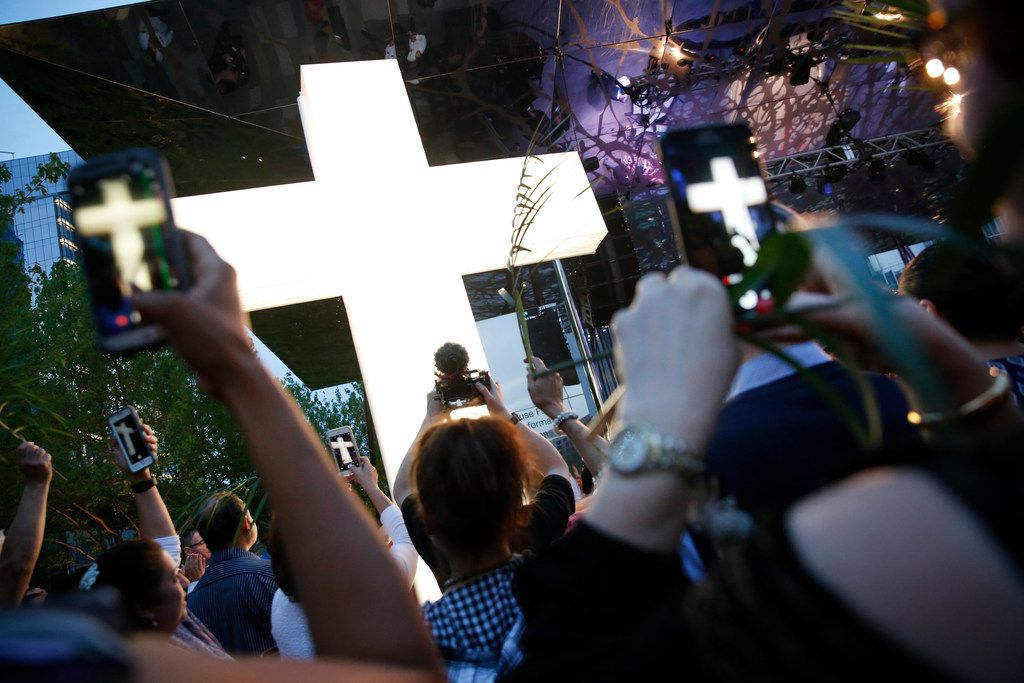 An illuminated cross is erected during the March for Eternal Life led by members of First Baptist Dallas at Klyde Warren Park in Dallas on Palm Sunday, March 25, 2018. The march comes a day after the March for Our Lives protests for stricter gun control. (Rose Baca/The Dallas Morning News)