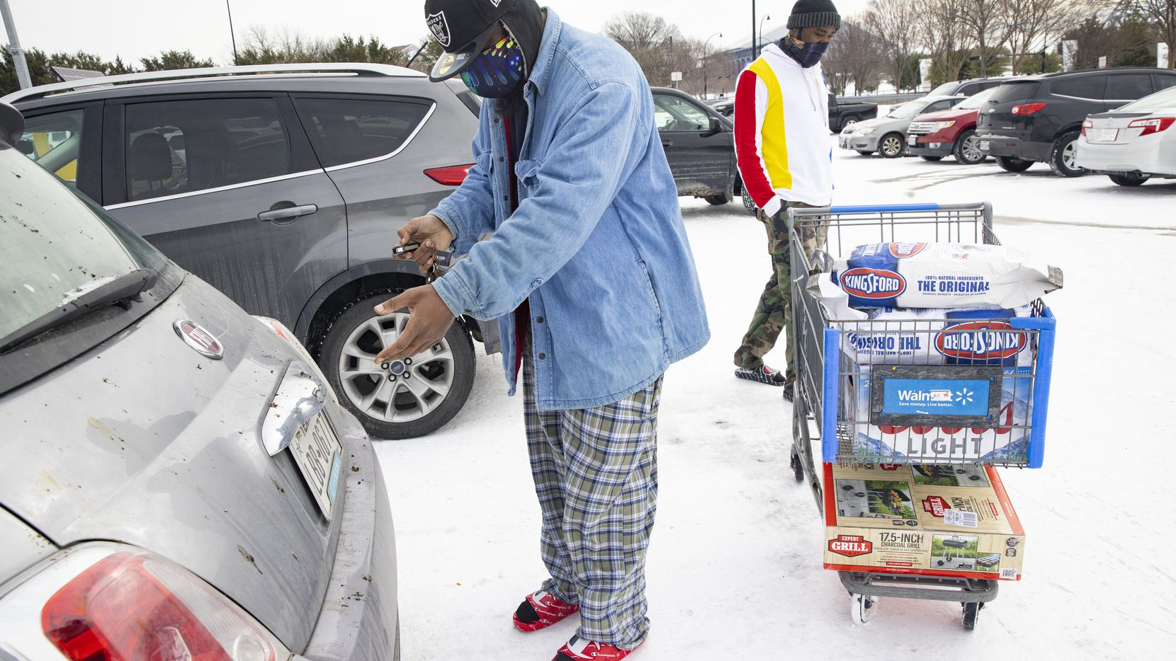 Reuben Brown (left) and Dekaetron McCalley wheel charcoal and a grill they bought at Walmart to their car at Walmart in Arlington on Feb. 16, 2021. They lost power yesterday and plan to use the charcoal and grill to cook food.
