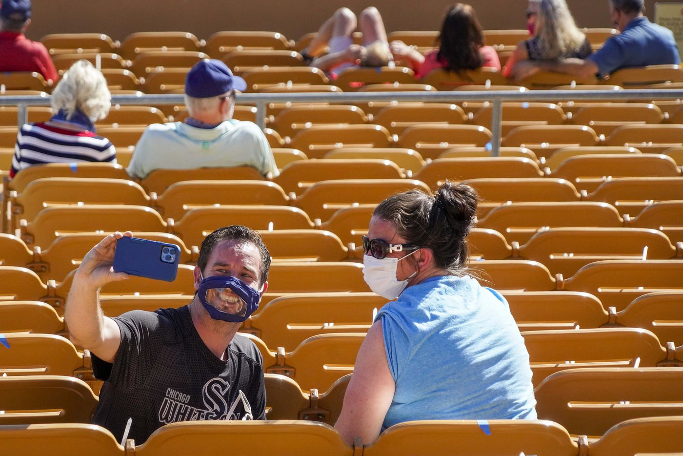 Socially distant mask wearing fans take a selfie during the sixth inning of a spring training game between the Texas Rangers and the Chicago White Sox at Camelback Ranch on Tuesday, March 2, 2021, in Phoenix, Ariz.