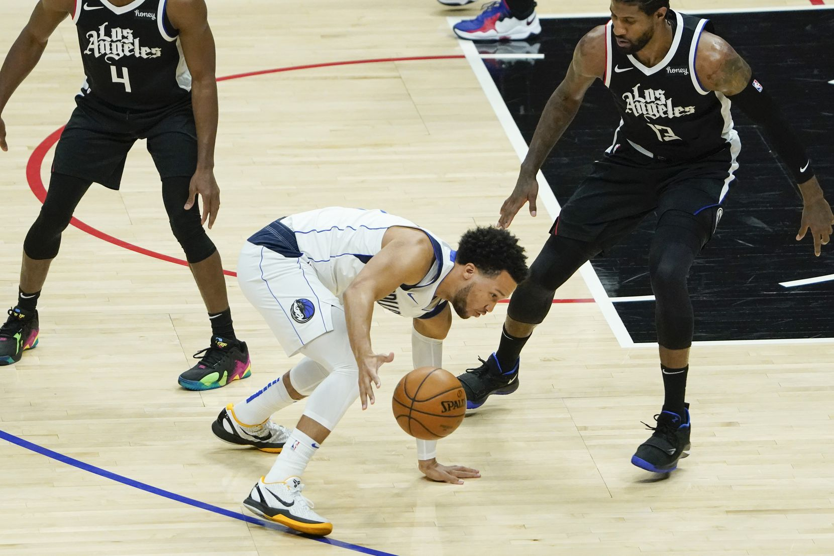 Dallas Mavericks guard Jalen Brunson (13) slips to the floor as he works against LA Clippers guard Paul George during the first quarter of an NBA playoff basketball game at the Staples Center on Wednesday, June 2, 2021, in Los Angeles.  (Smiley N. Pool/The Dallas Morning News)
