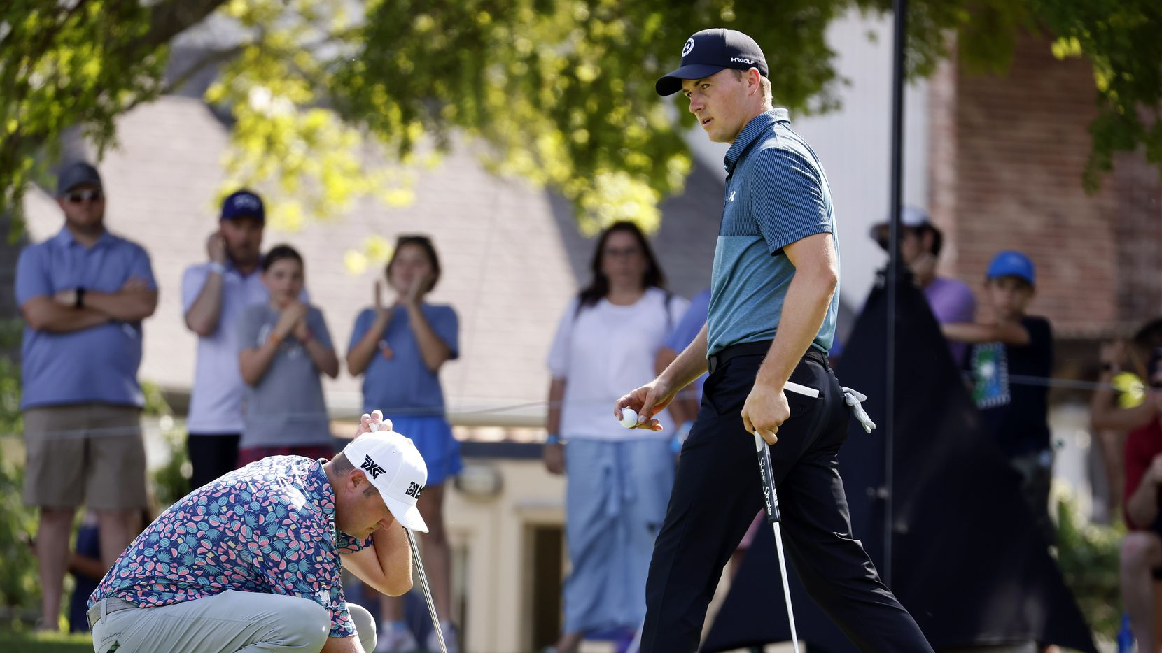 Professional golfer Jordan Spieth (right) walks off the 14th green as Jason Kokrak places his ball during round three of the Charles Schwab Challenge at the Colonial Country Club in Fort Worth, Saturday, May 29, 2021. Spieth held a one shot lead over Kokrak at 15-under.