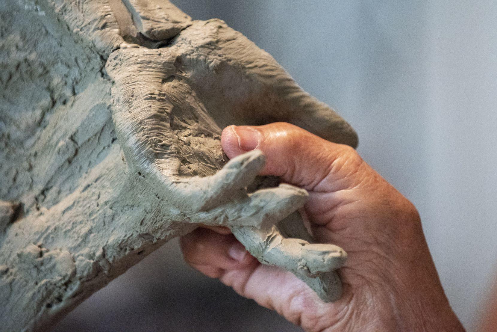 Bessie Rodriguez coloca su dedo sobre la mano de la escultura de su hijo Santos, hecha por Seth Vandable. La mujer de 77 años pudo conocer la estatua esta semana por primera vez en su domicilio de Cedar Hill.
