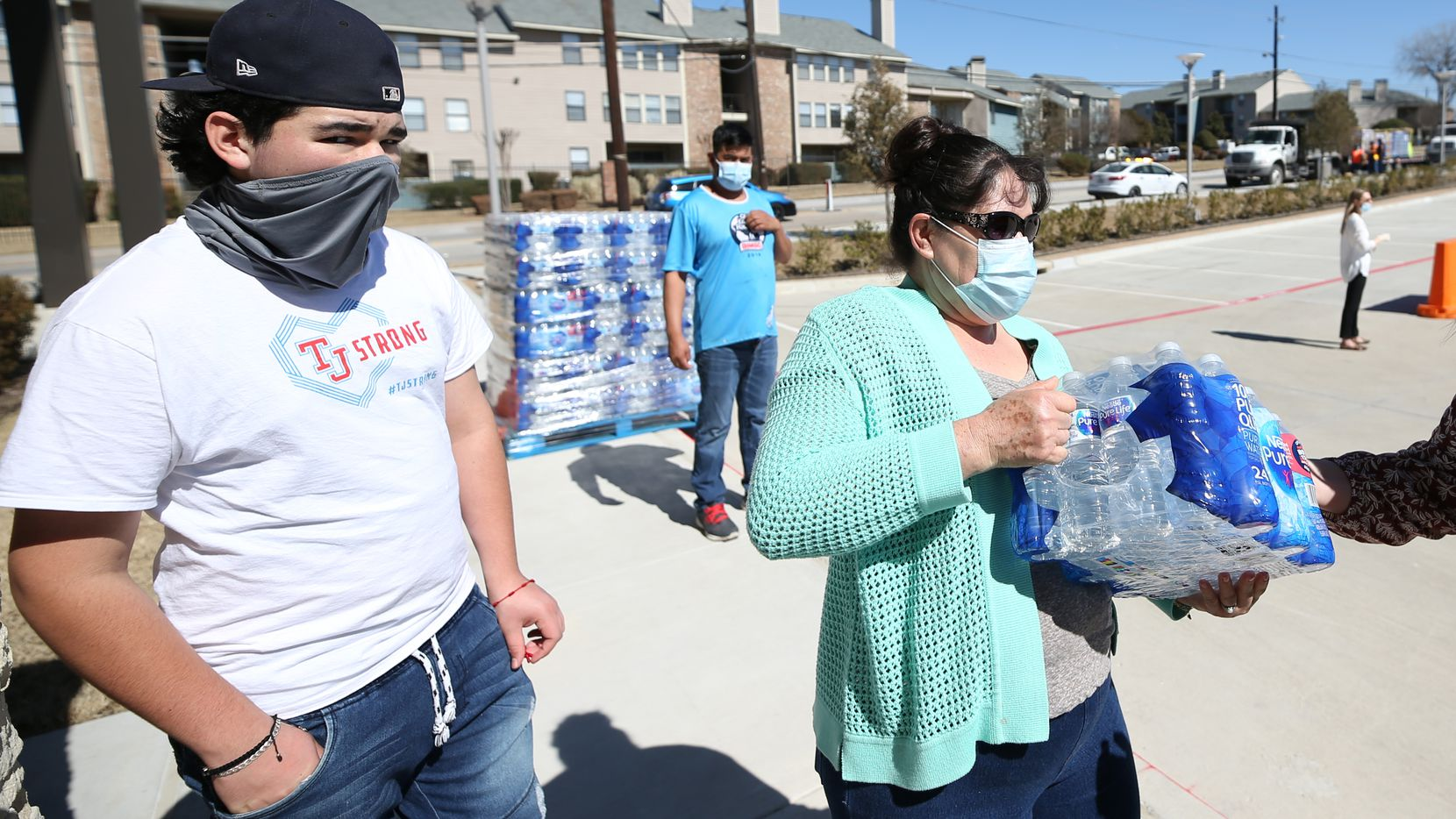 Area resident Belia Ornelas, 50 (right), receives bottled water from the Dallas Office of Emergency Management, which delivered 12 pallets of bottled water that were distributed at The Buckner Family Hope Center on Feb. 23, 2021 in Dallas. (Photo Omar Vega / Al Dia)