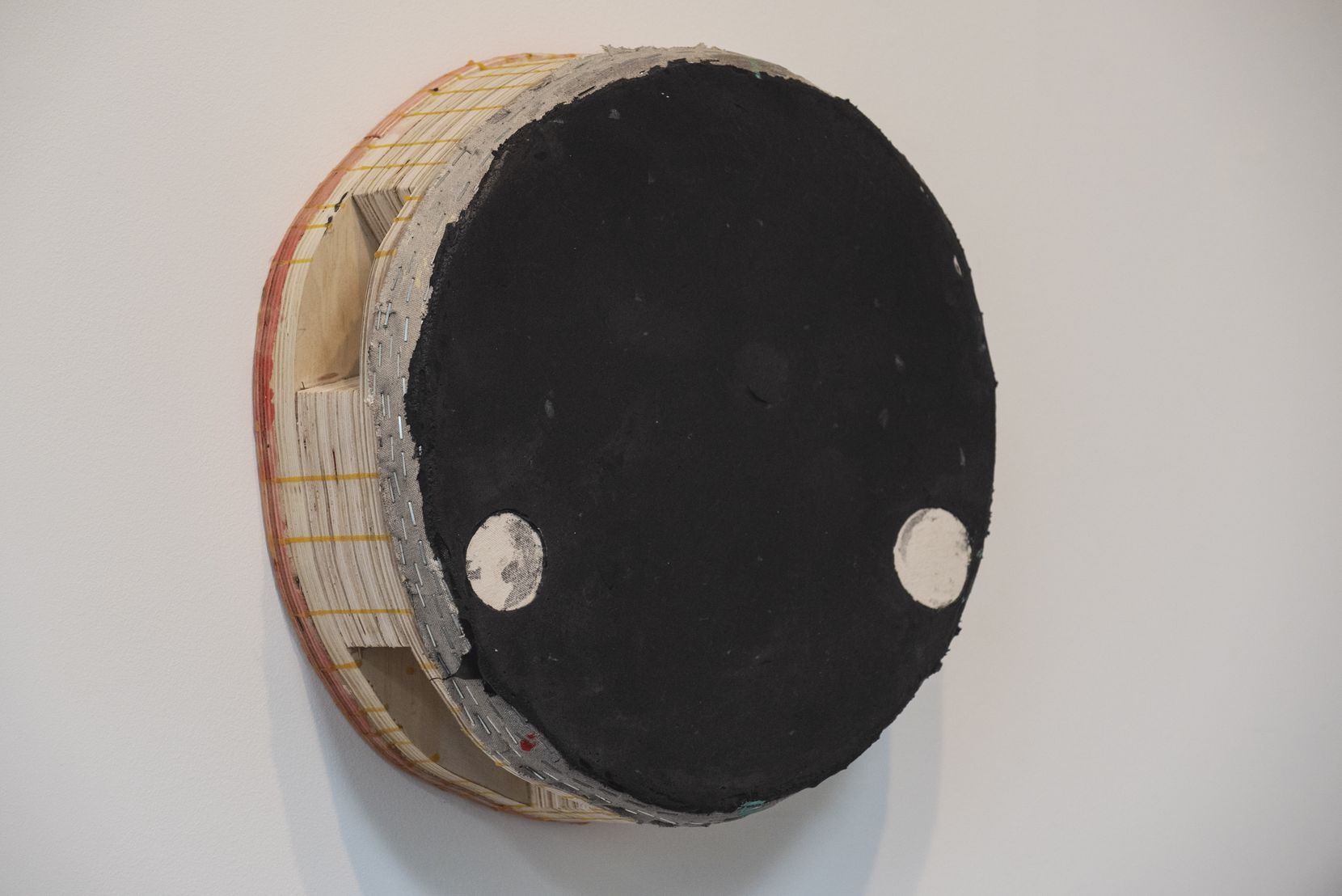 "Unlike many purists, Otis Jones is comfortable with things like unprimed canvas and the presence of staples and glue in his works such as ""Black Circle with Two Raw Canvas Circles."""