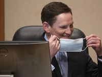 Dallas County Judge Clay Jenkins switches masks during a Dallas County Commissioners Court meeting at the Dallas County Administration Building in Dallas on Tuesday, May 18, 2021. (Lynda M. González/The Dallas Morning News)