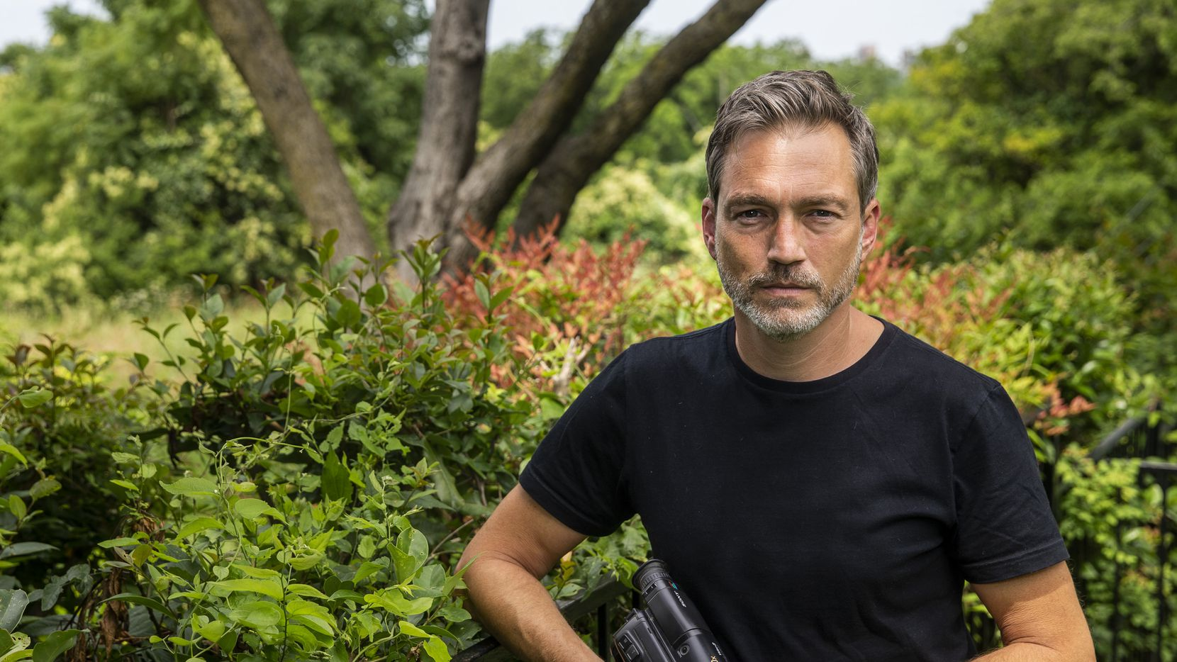 """Filmmaker Miles Hargrove holds the Sony Video8 camcorder he used to film the 25-year-old footage in his new film, """"Miracle Fishing,"""" during a portrait session at his home in Dallas on Thursday, May 28, 2020."""