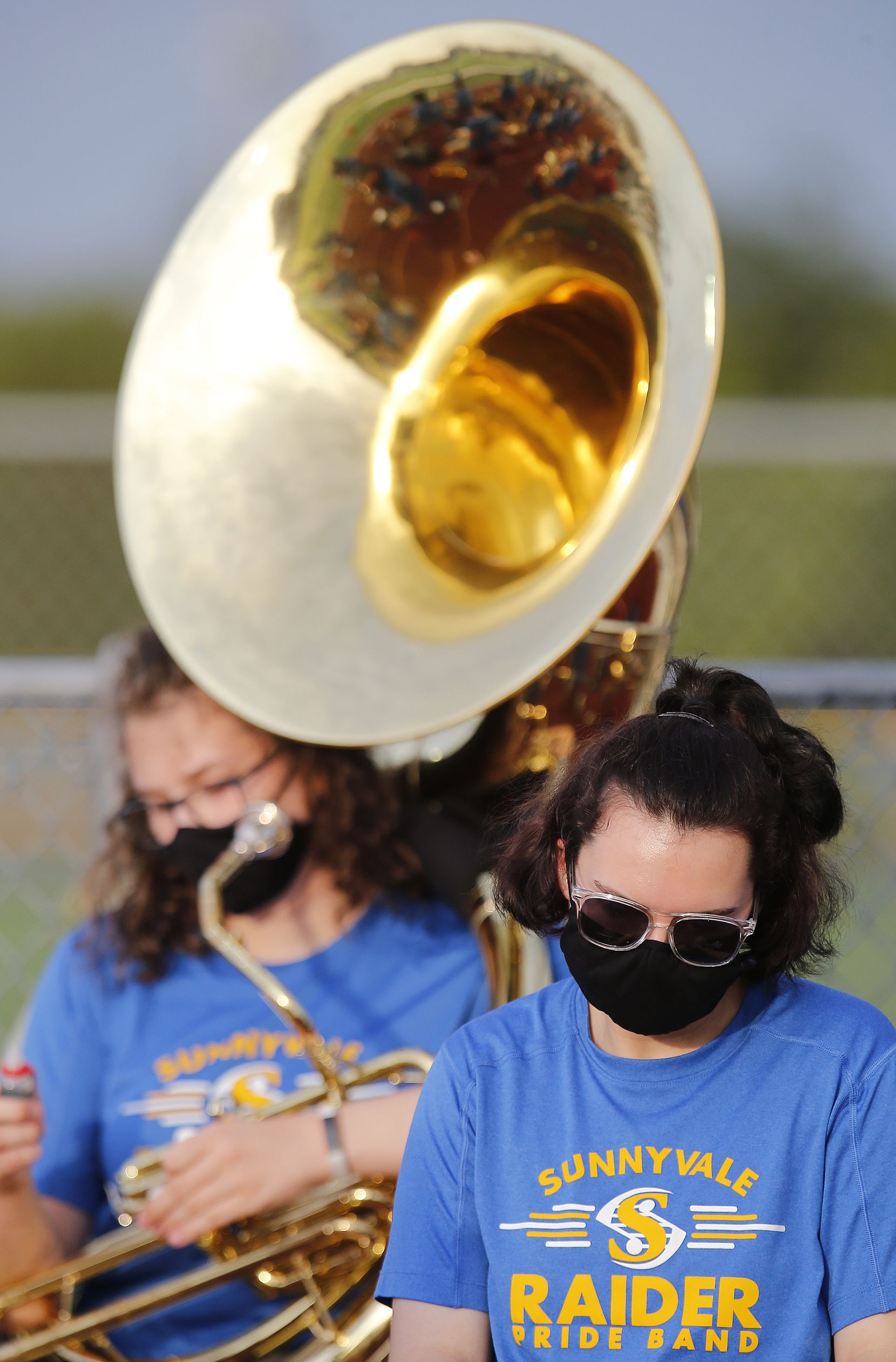 Lynsie Coning, 17, with a sousaphone, and Cadence Houghton, 17, a trumpet player, were members of the Sunnyvale High School marching band wearing masks as they take a break during warm ups as Melissa High School hosted Sunnyvale High School at Melissa I.S.D. Stadium on Friday night, September 4, 2020.  (Stewart F. House/Special Contributor)