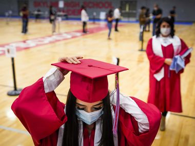 Senior Tania Pelaez Ramirez prepares to have her photo taken for use in the school's virtual graduation ceremony as student pick up their graduation caps and gowns at Skyline High School on Monday, May 11, 2020, in Dallas. Lawmakers are discussing alternate paths to graduation for some high school seniors.