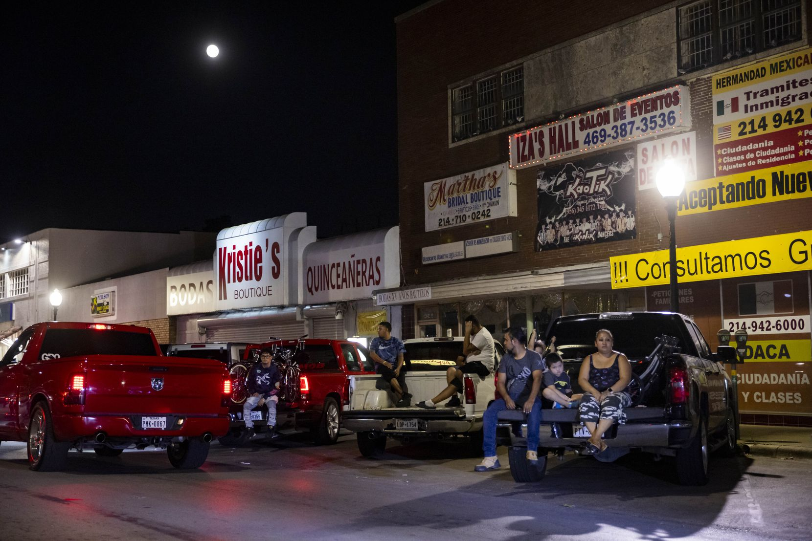 Familes watch as people cruise in their cars on Sunday, Sept. 19, 2021, on Jefferson Boulevard in Dallas.