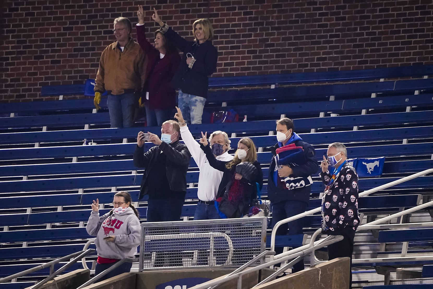 SMU fan Paul Layne (center. in white shirt) stands for the playing of the school's alma mater following a game against Navy at Ford Stadium on Saturday, Oct. 31, 2020, in Dallas.