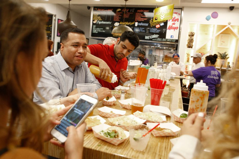 Edgar Vasquez (center) and Raul Santillan (left) eat at Salsa Limon in Dallas on March 16, 2017. It just opened in downtown Dallas.