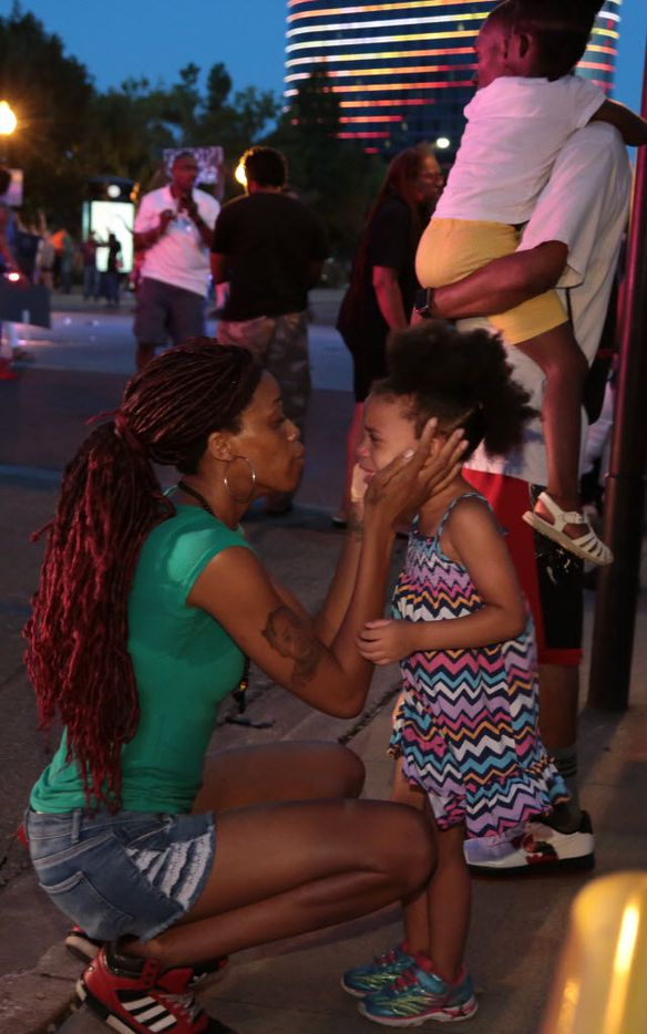A mother tries to calm her daughter as Dallas police respond to shots being fired during a protest over recent fatal shootings by police in Louisiana and Minnesota,Thursday, July 7, 2016, in Dallas. Snipers opened fire on police officers during protests; several officers were killed, police said. (Maria R. Olivas/The Dallas Morning News via AP)