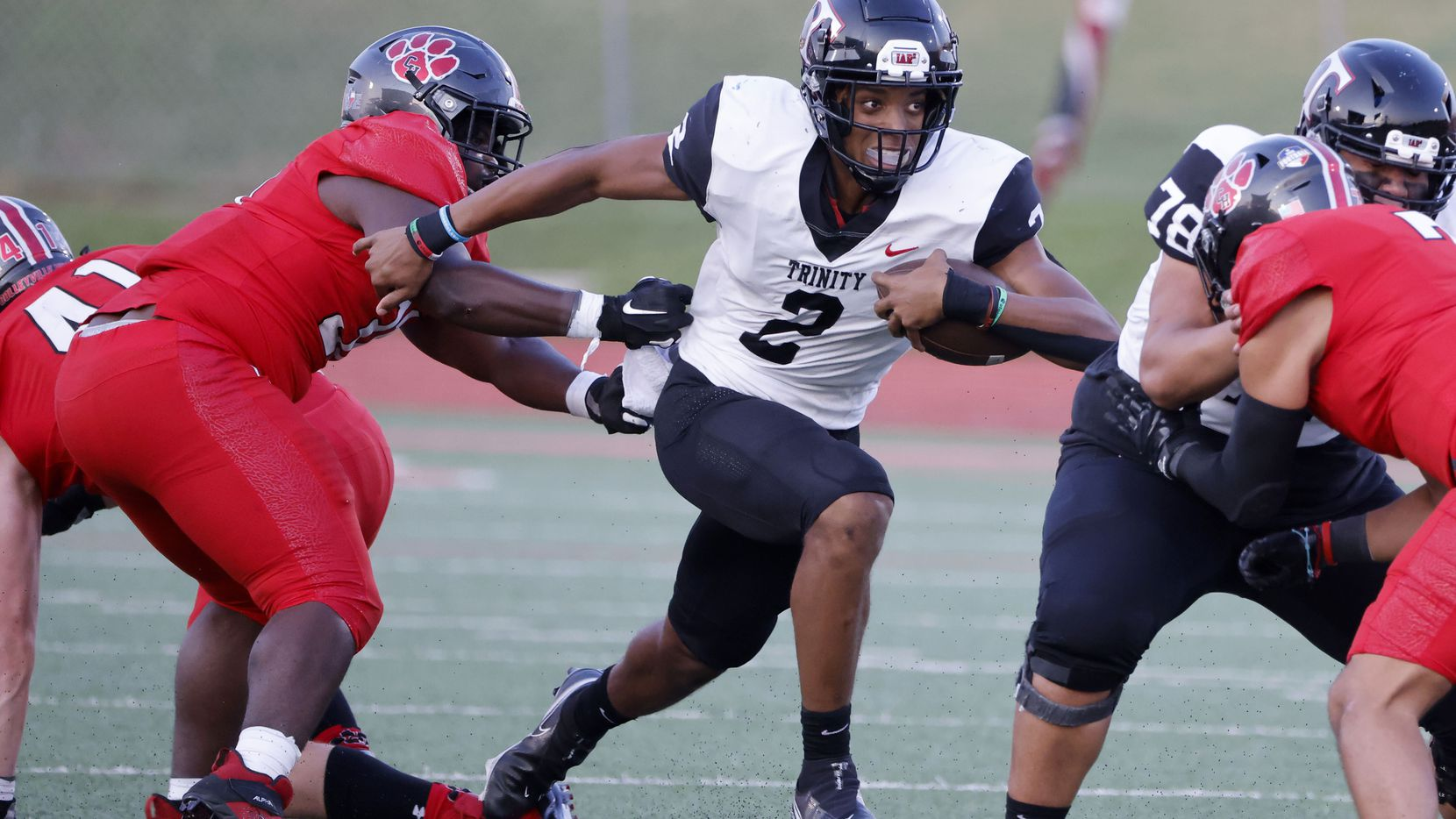 Colleyville defender Elijah Omar (left) tries to stop Euless Trinity quarterback Ollie Gordon (2) during the first half of a high school football game in Grapevine, Texas on Friday, Sept. 10, 2021.
