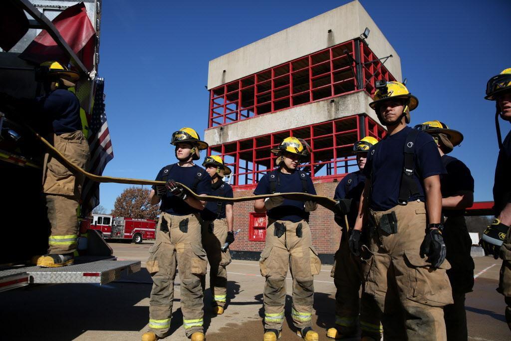 Los aprendices de bomberos preparan una manguera durante un entrenamiento en Dallas. ROSE BACA/DMN
