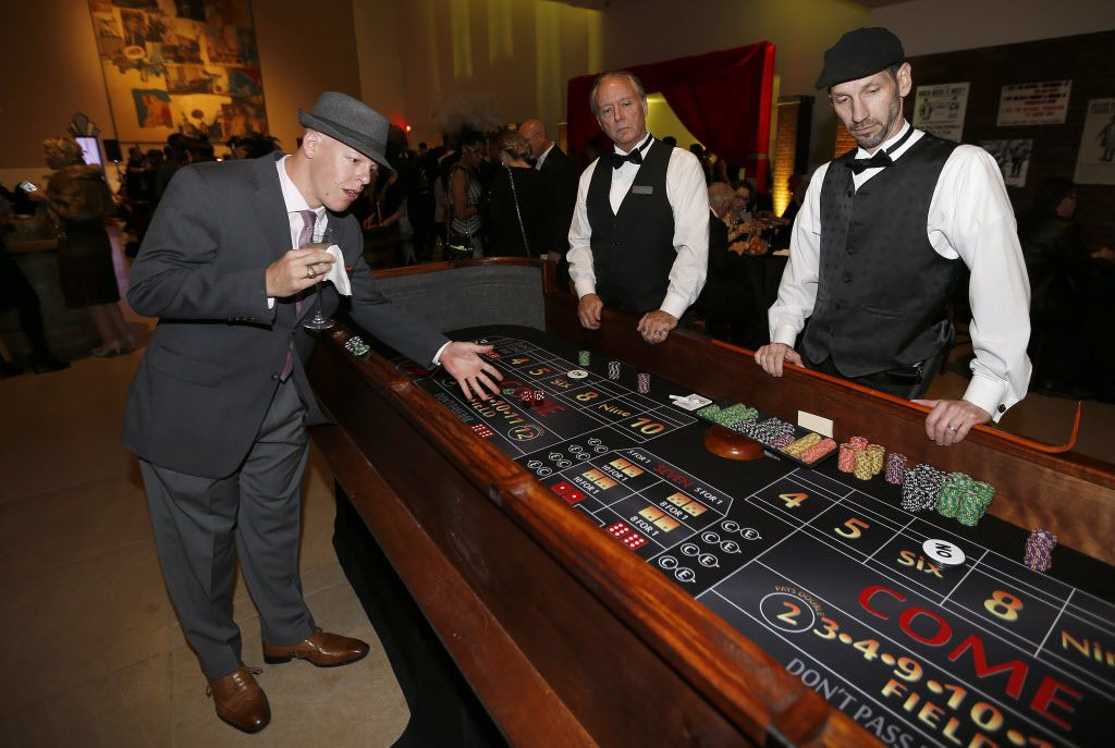 Robert Dechant (left) plays craps during the DMA Speakeasy event in celebration of Shaken Stirred Styled: The Art of the Cocktail at Dallas Museum of Art in Dallas, Saturday, Feb. 4, 2017. (Jae S. Lee/The Dallas Morning News)