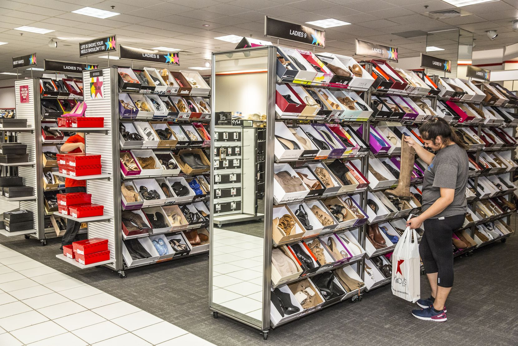 Carmen Patlan shopping for women's shoes in the new Macy's Backstage Town East Mall which features an expanded assortment of shoes for kids, women and men as well as home décor, bath and beauty products, toys, tech, gadgets and more. (Shannon Faulk/AP Images for Macy's)